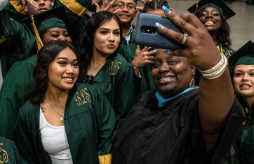 Math teacher Ciara Redfearn (right) takes a group photo with students before the 2019 commencement ceremonies for Smith High School at the Greensboro Coliseum Special Events Center in Greensboro, N.C., on Saturday, June 8, 2019.